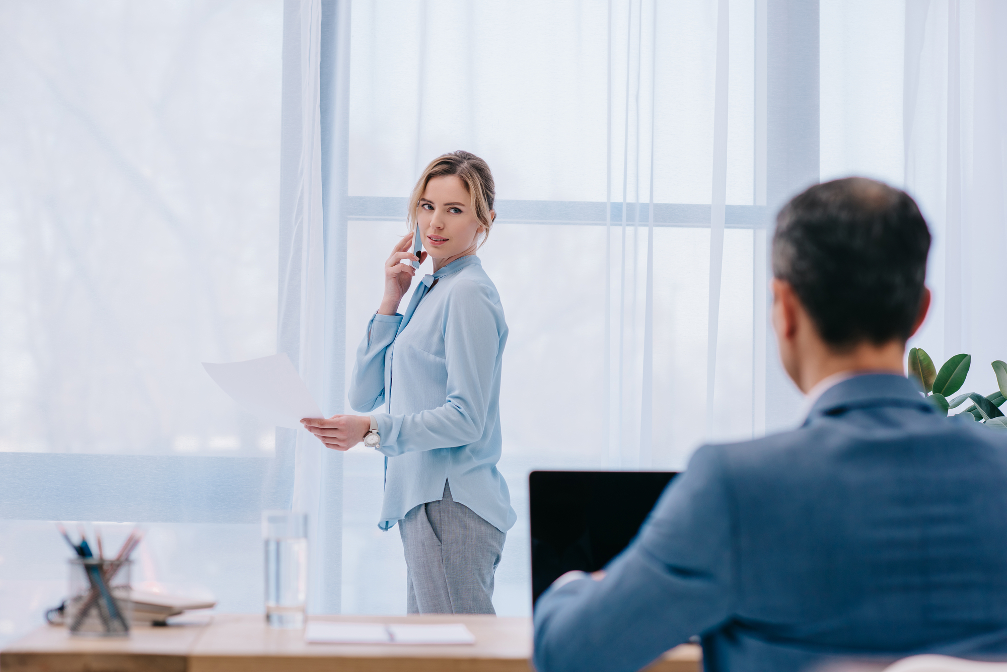 Businesswoman talking by phone at office while her colleague working with laptop on foreground