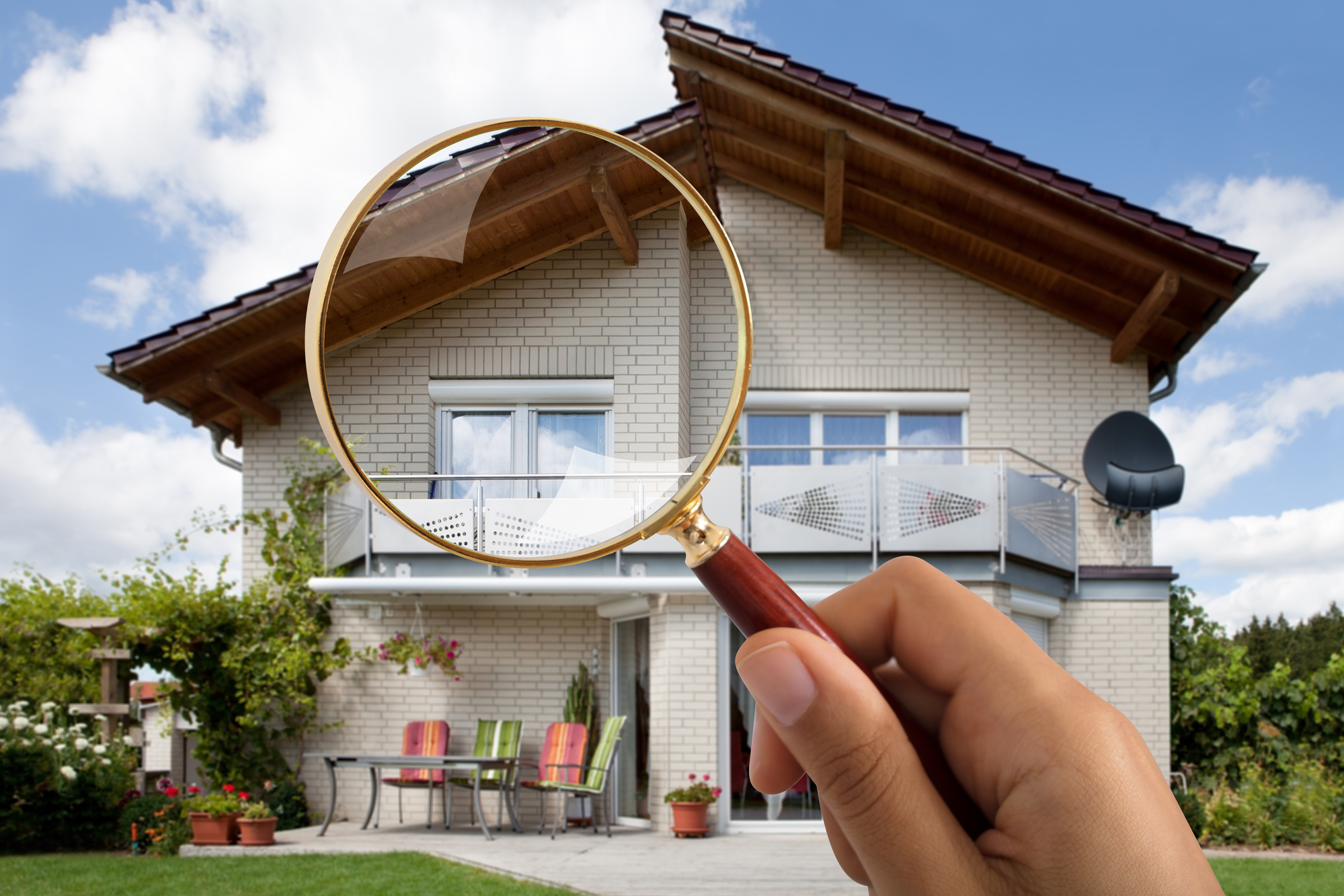 Close-up Of Persons Hand Holding Magnifying Glass Over Luxury House Outdoors