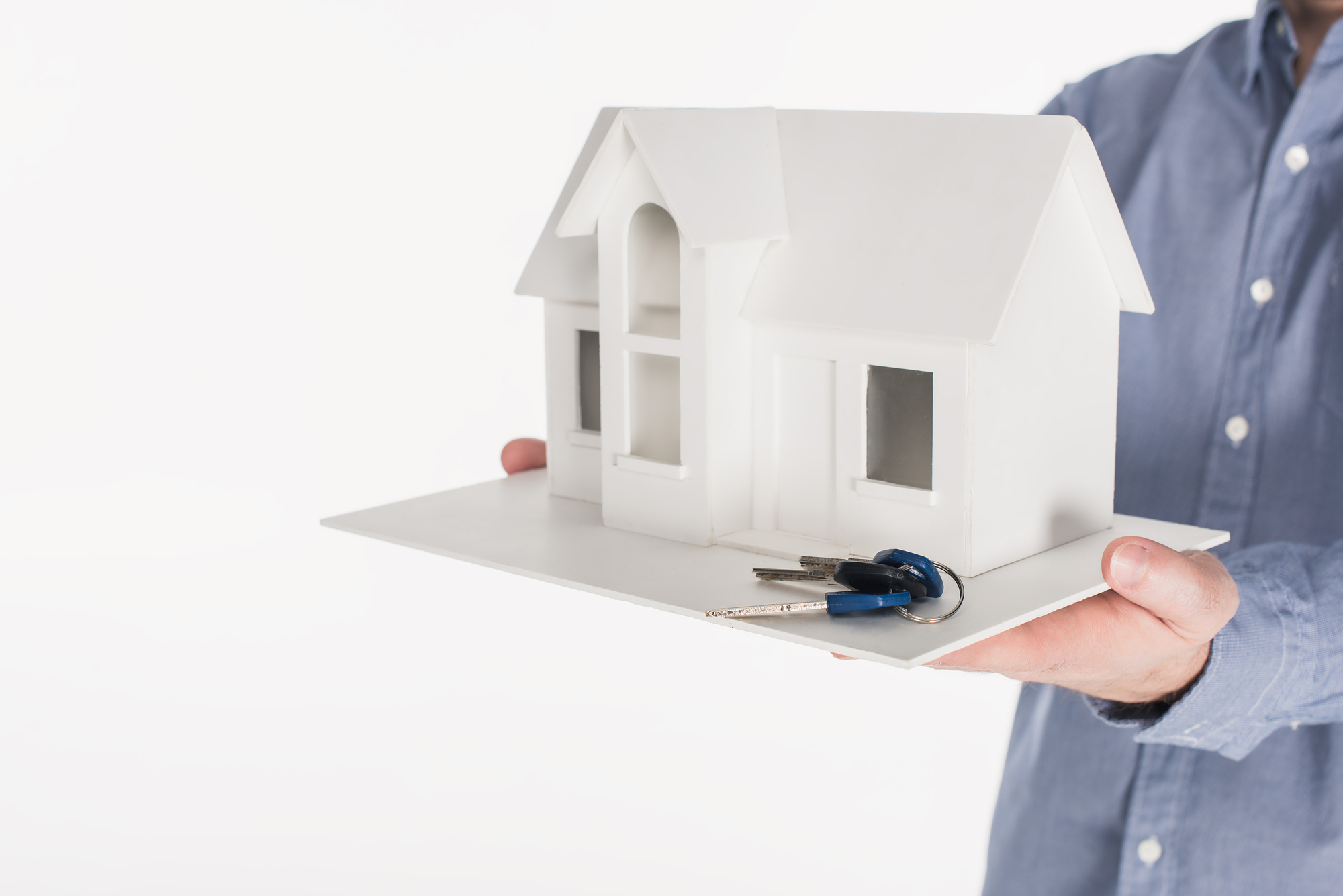 Cropped man holding miniature house with keys