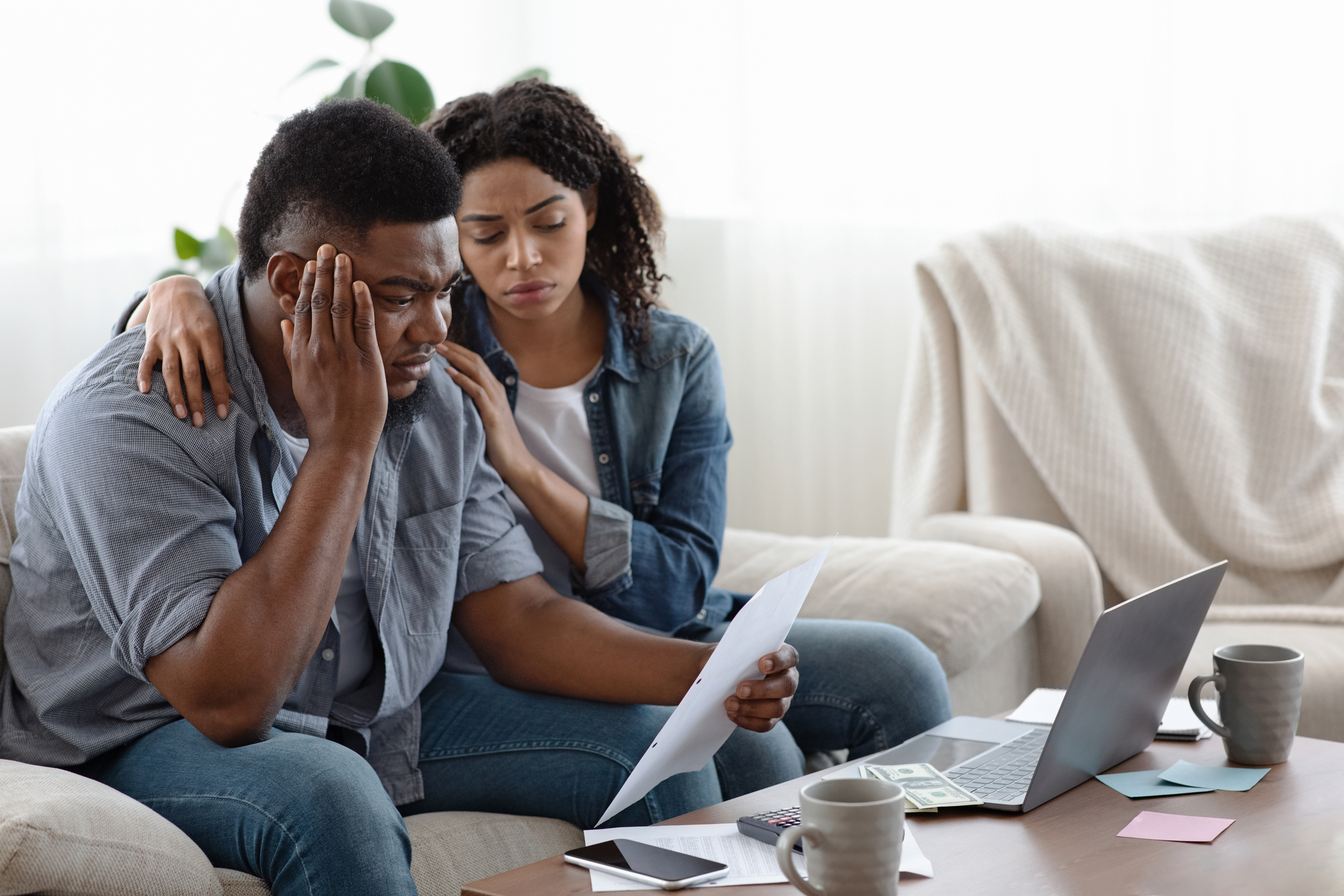Financial Crisis. Depressed black couple sitting with huge bills in living room