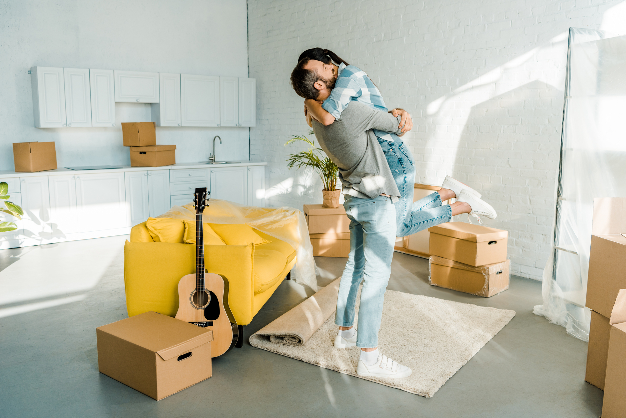 Happy husband hugging wife while packing for new house, moving concept