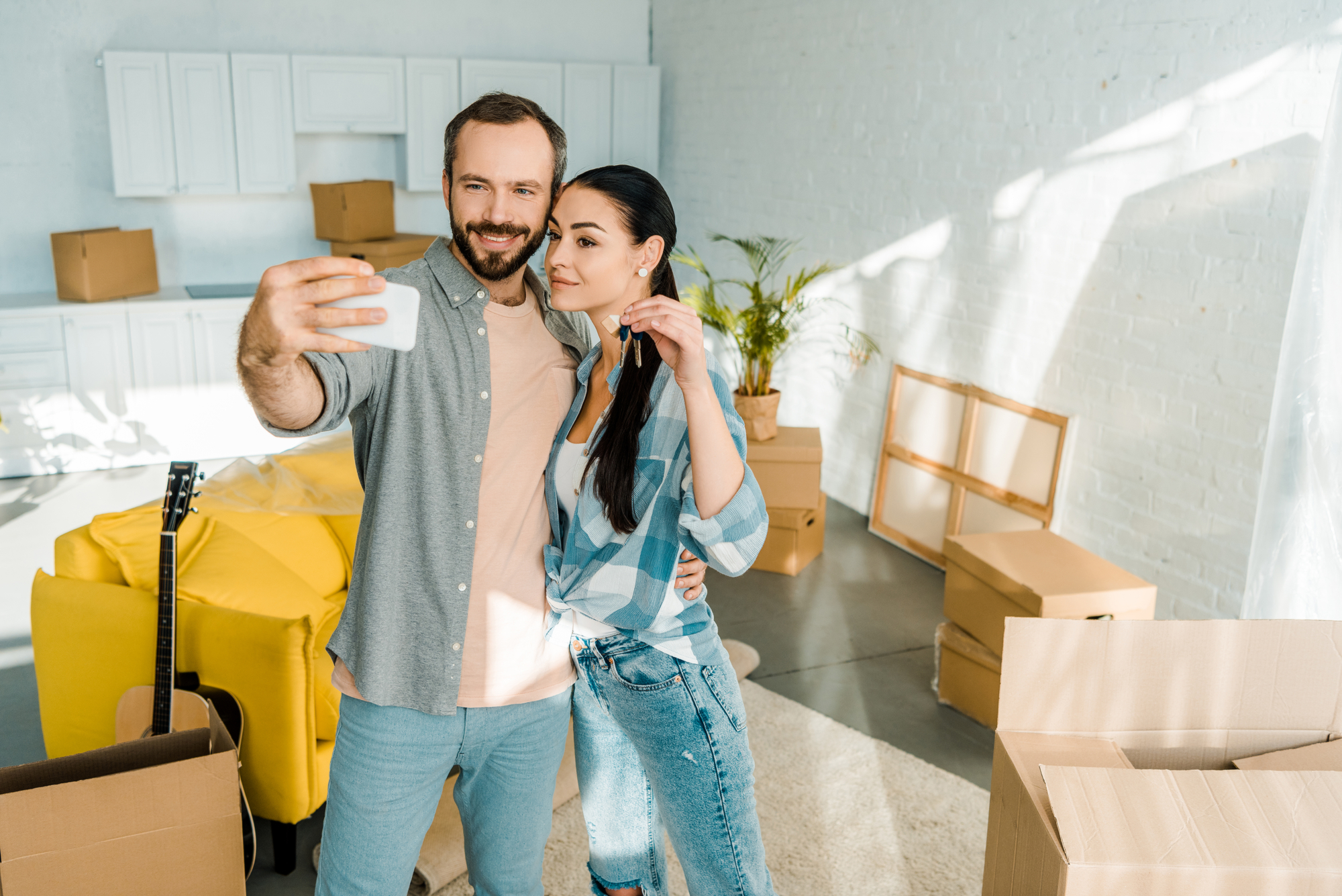 Happy moving couple taking selfie on smartphone while wife holding keys from new house