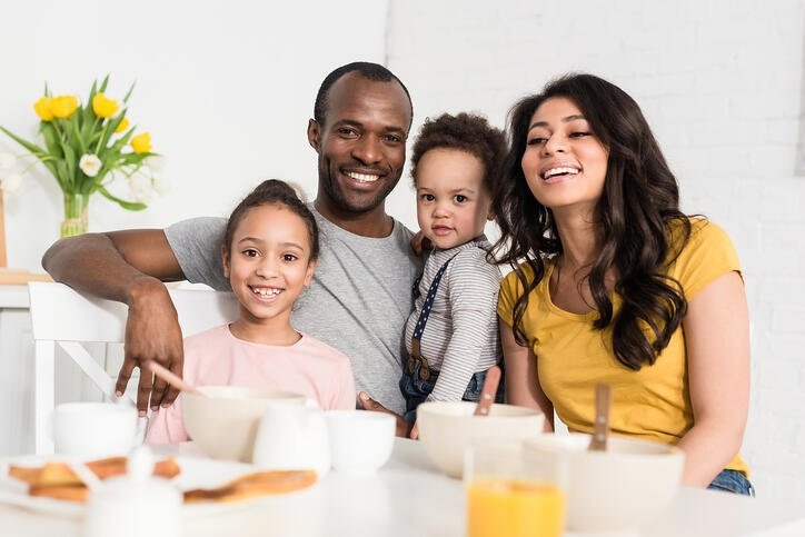 Happy young family having breakfast together and looking at camera