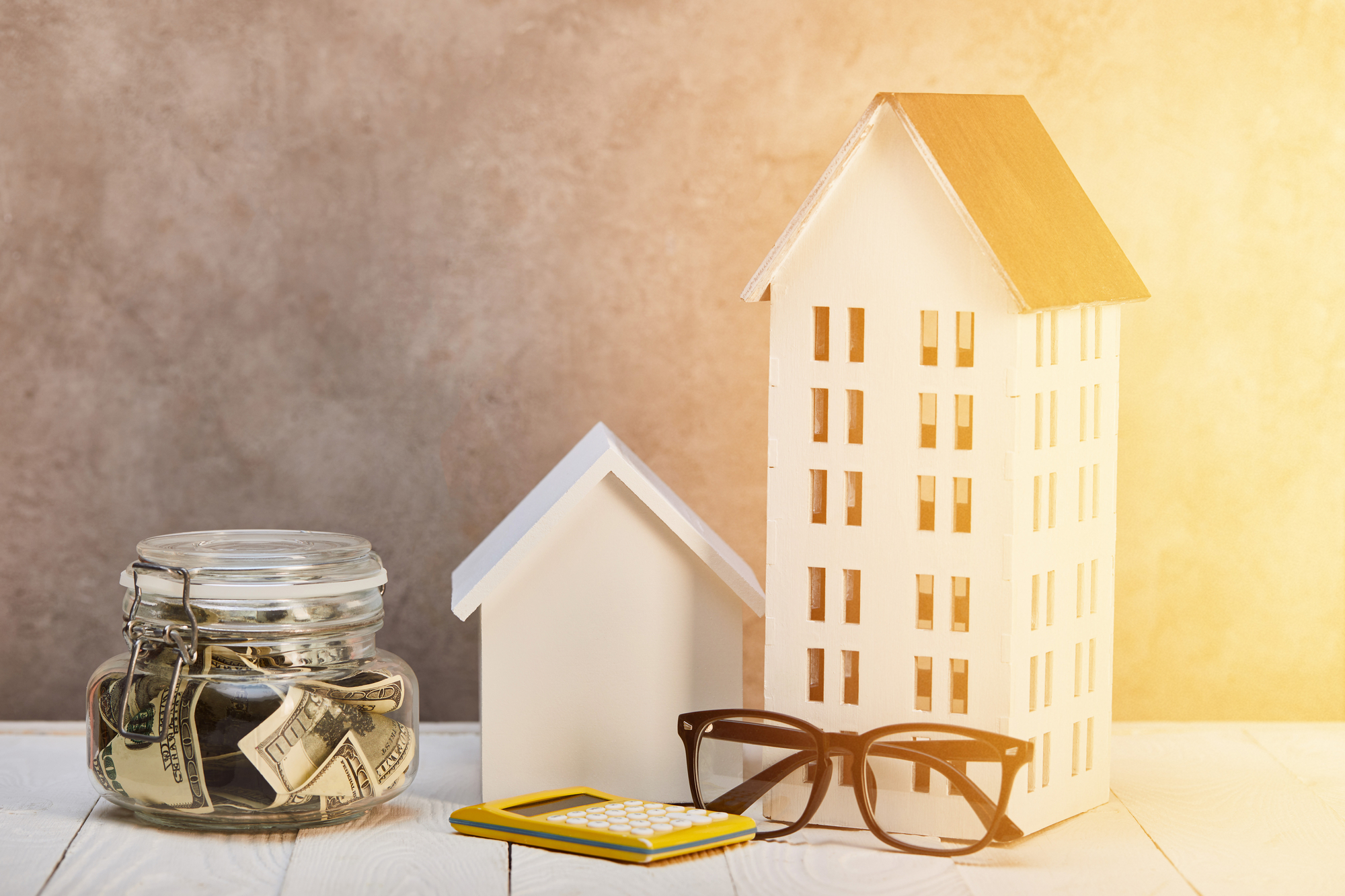 Houses models on white wooden table with glasses, calculator and moneybox in sunshine, real estate concept
