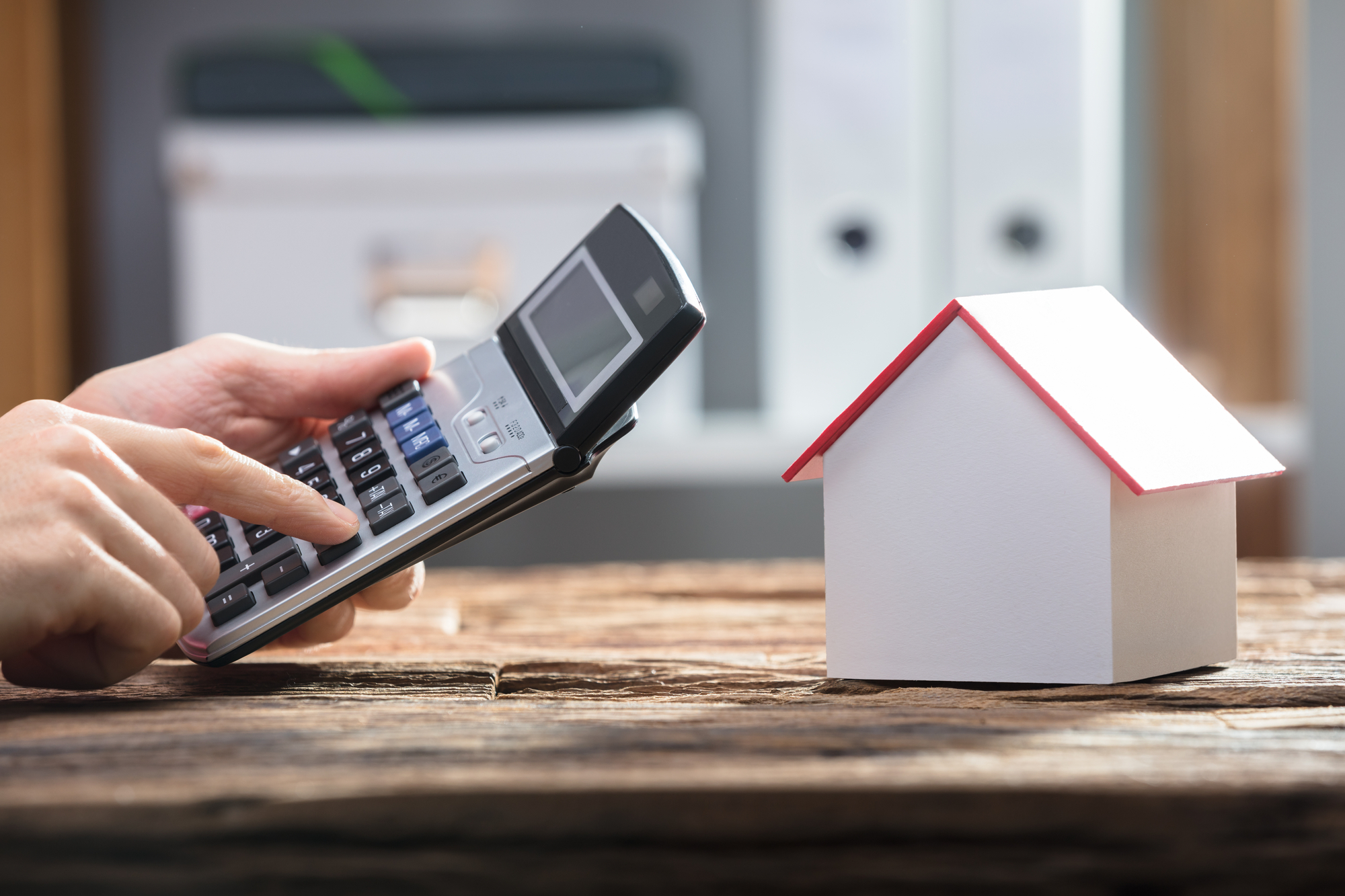Human Hand Using Calculator With House Model On Wooden Desk