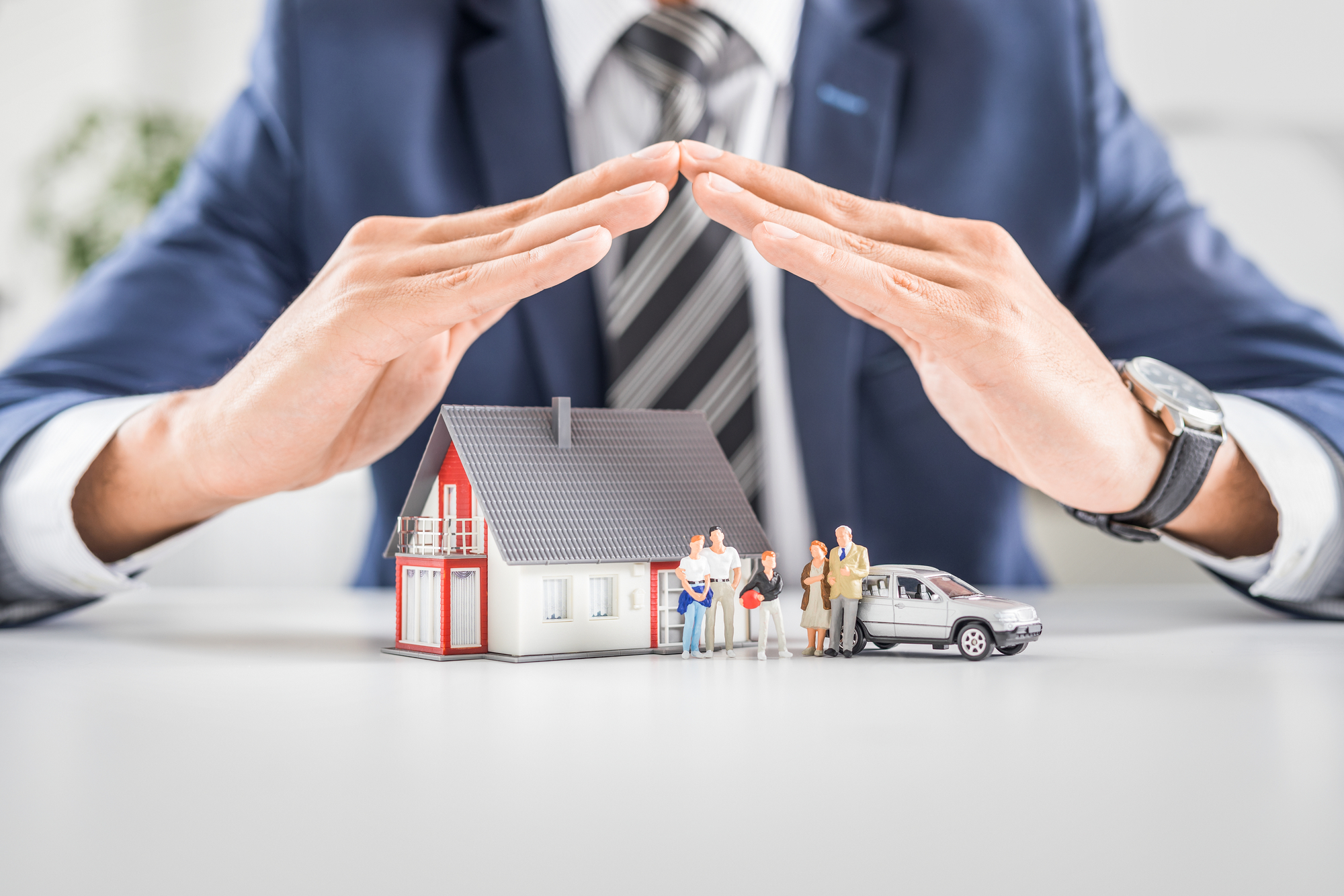 Insurance agent with house toy, safety insurance concept