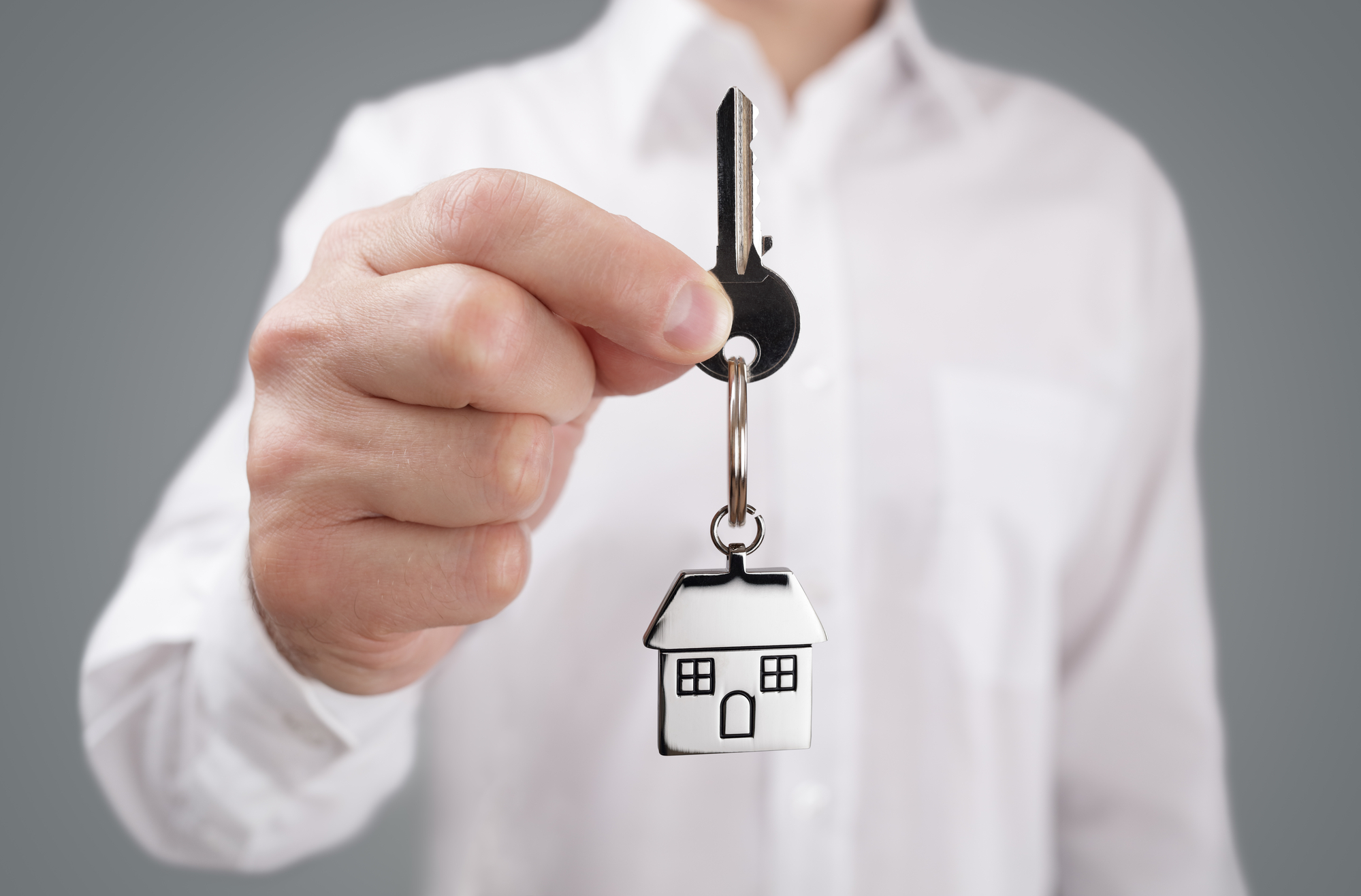 Man holding out house key