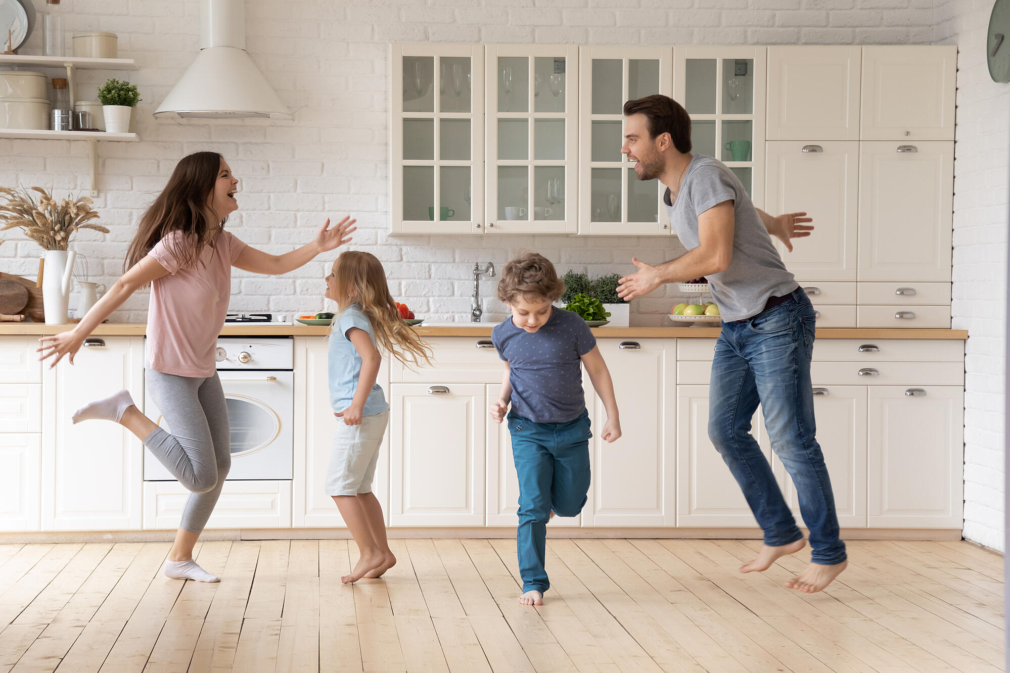 Overjoyed young family dancing with little kids at home