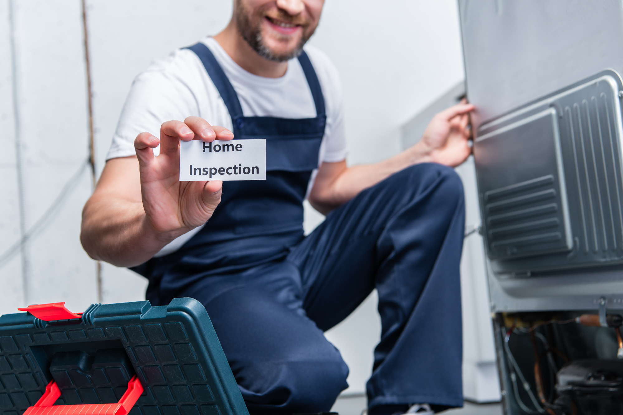 Partial view of adult craftsman showing card with lettering home inspection while sitting near broken refrigerator