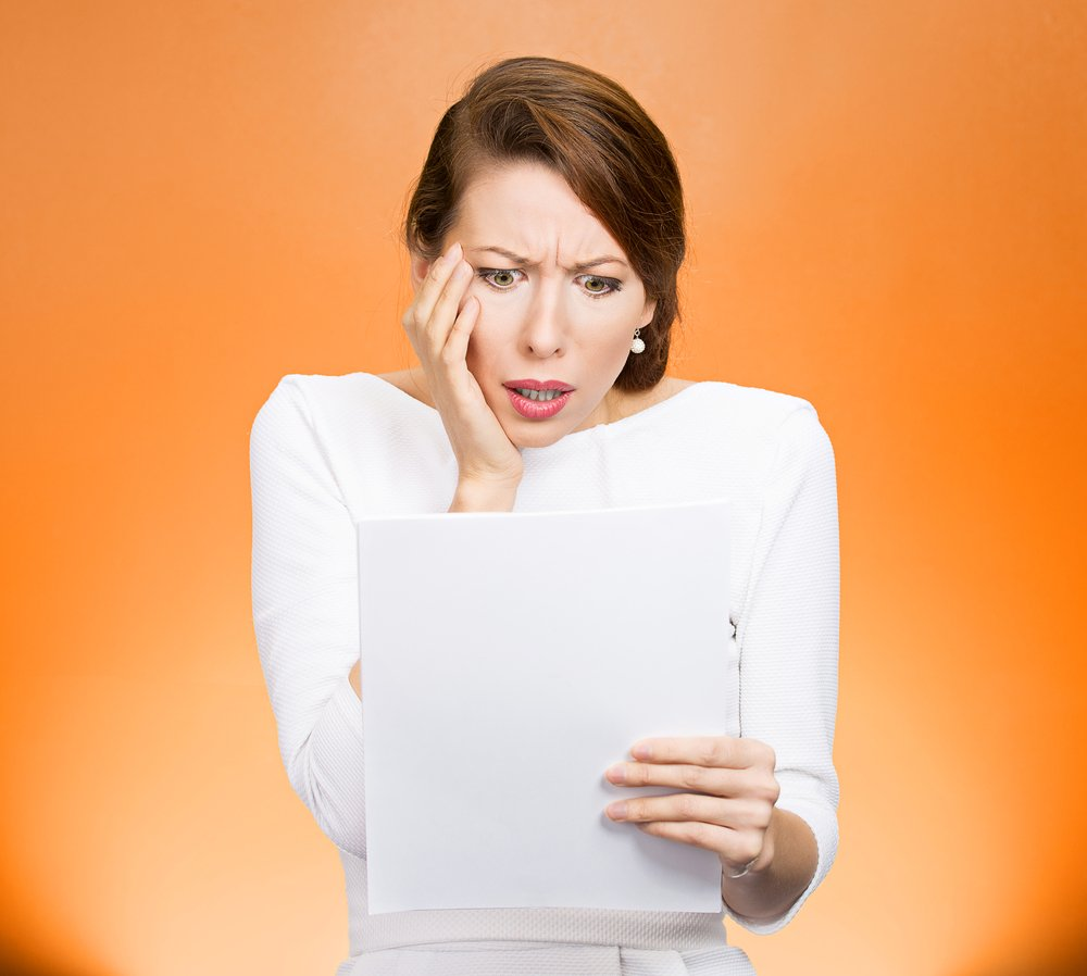 Closeup portrait shocked, funny looking young woman, disgusted at monthly statement, test, application, results isolated orange background. Negative human emotion, facial expression, feeling. Bad news